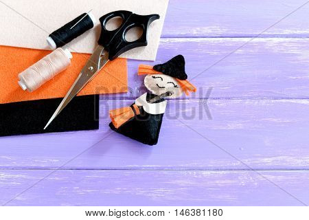 Adorable Halloween witch made of felt, scissors, thread set, orange, beige and black felt sheets on wooden background with copy space for text. Halloween crafts idea for kids. Inspiration crafts