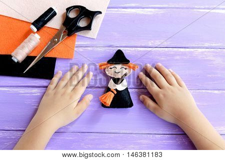 Child shows a Halloween witch doll. Child put his hands on a wooden table. Needlework supplies. Original witch crafts for kids. Idea for home ornament. Halloween crafts and activities