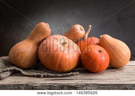 still life of pumpkins on a wooden board.
