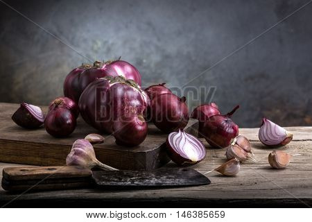 still life of vegetables on a wooden board. red onion, garlic, eggplant.