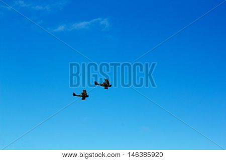 Pair Of Biplanes Against A Blue Sky
