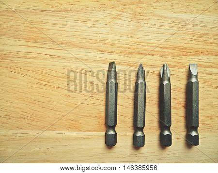 Set of screwdriver bit on wooden background
