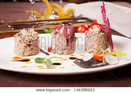 duck pate with sauce on white plate in restaurant