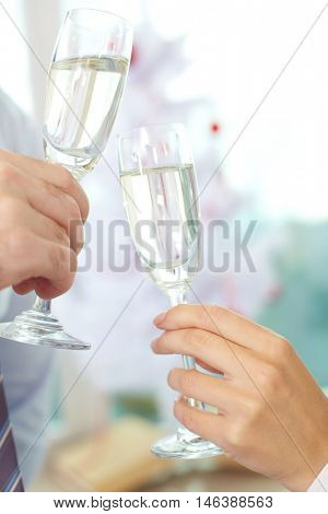 Close up of man and woman clinking tall champagne glasses during celebration toast, Christmas tree in background