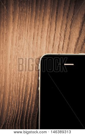 Milan Italy - September 3 2014: Apple iphone 4 smartphone on a wood surface front view from above