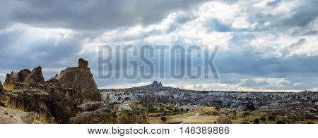 Beauty geological formations in Cappadocia, Turkey. Rays of lights cast down from cloudy sky in Cappadocia valley, among mountains in Goreme National Park.  Typical terrain landscape in Cappadocia