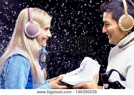 Smiling man giving figure skates to happy woman