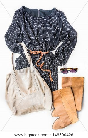Top view of woman clothing set. Black dotted dress brown leather boots and accessories over white wood background.