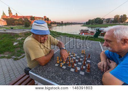 KRAKOW, POLAND - FEB 8, 2016: Unidentified elderly mens play chess on the embankment of Vistula.