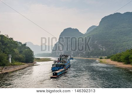 Xingping China - October 20 2013: A tourist boats packed with tourists travels the magnificent scenic route along the Li river from Guilin to Yangshou in the haze.