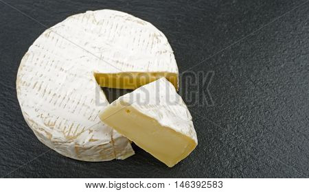 french cheese - round camembert with cut slice, on rough graphite background