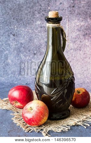 Bottle with apple vinegar and apples on the burlap on a blue background.