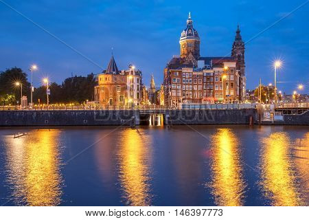 Night city view of Amsterdam canal and Basilica of Saint Nicholas, Schreierstoren or Weepers Tower and Oude Kerk, Holland, Netherlands.