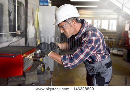 Metalworker with security helmet in workshop