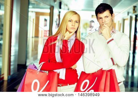 Young doubted couple with shopping bags standing at the showcase