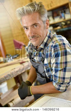 Carpenter working wood in workshop