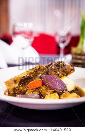 Romantic dinner - Roasted lamb shank with seasonal vegetables in a stylish restaurant setting