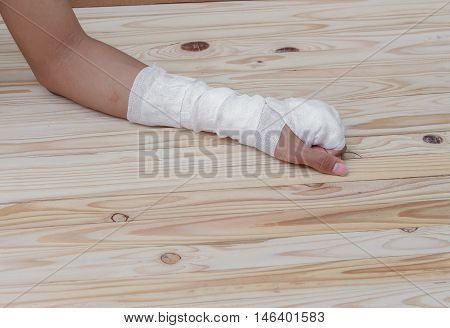 Gauze bandage the hand contusion. treating patients with hand with a wrist left male, On a wooden table