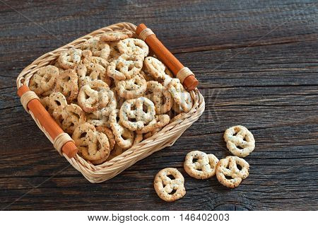 Salty pretzels with cheese and poppy in basket on dark wooden table. Delicious snack for beer