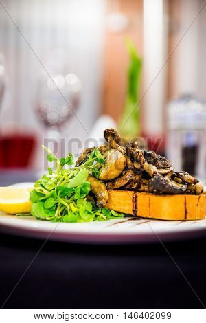 Gourmet grilled mushrooms on toasted bread in a lovely restaurant setting