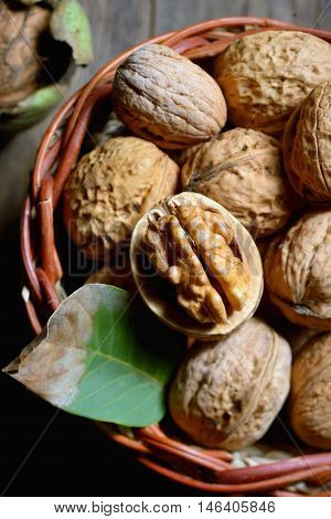 Walnut in basket and whole walnuts on rustic old wood