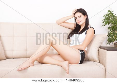 Relaxing woman sitting comfortable in sofa lounge chair smiling happy looking at camera. Resting beautiful young multicultural asian caucasian girl in her 20s .