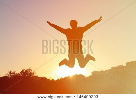 Silhouette of man jumping at sunset sky, happiness and success