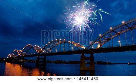 Fireworks at night over the Mississippi River bridge.
