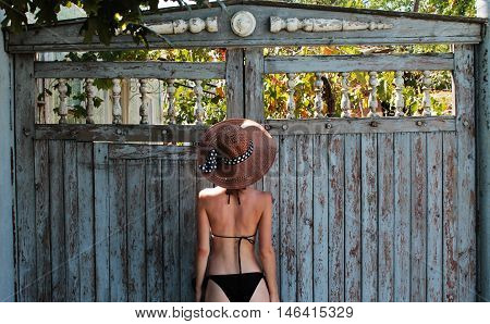 girl in a black bathing suit and hat standing near the blue gate