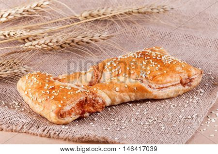 Delicious Puff Pastry With Cheese Filling And Sesame Seeds On Rustic Background With Spikelets. Past