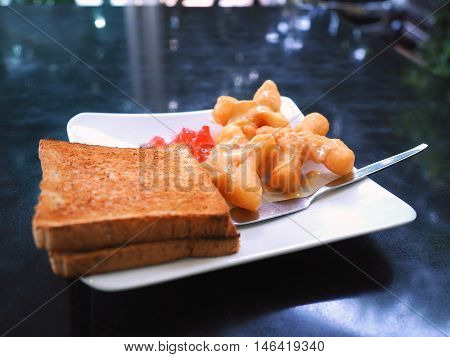 Breakfast with deep-fried dough stick or Patongko with Sweetened condensed milk and toast with strawberry jam