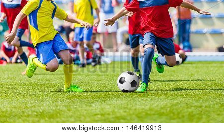 Youth football soccer match. Kids playing soccer game on sport field. Boys kicking football match on pitch. Sports soccer background.