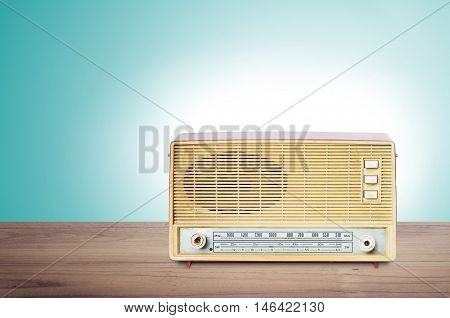 Old Dusty Radio From 1970 On Wooden Table With Mint Green Background.