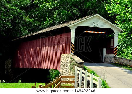 Christiana Pennsylvania - June 6 2015: 19th century Christiana Covered Bridge spans a small stream surrounded by verdant forests *