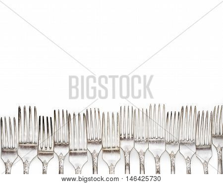Aged vintage silver forks border isolated on white background. Fork background.