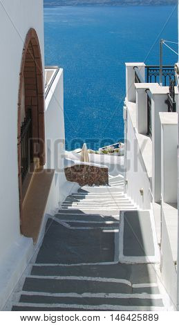 Traditional style stairway to the sea between houses of Santorini Greece