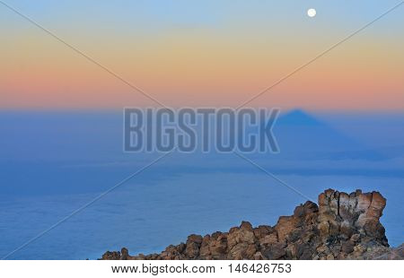 Landscape with stones, shadow of  Teide and moon in sunrise light. Tenerife, Canary islands, Spain