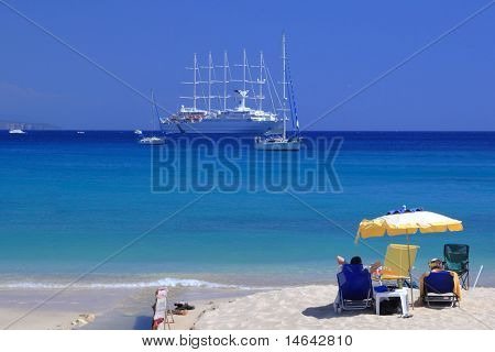Couple on the beach watching a luxurious cruiseship