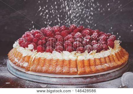 Raspberry and lemon cream tart with flaked almonds and fresh raspberries on top. Macro, selective focus, vintage toned image