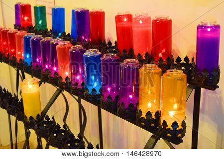 Row of colorful lit candles taken in a church for prayer