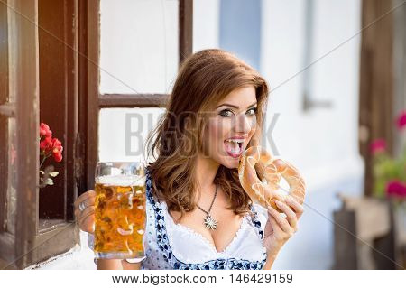 Beautiful young woman in traditional bavarian dress sitting on wooden bench holding a mug of beer and pretzel, eating it, against old country house. Oktoberfest.