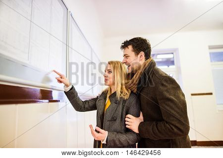 Beautiful young couple traveling, looking at timetable in bus waiting room, having fun together.