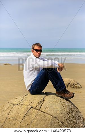 Young man sitting on top of one Moeraki Boulder on the Koekohe beach Eastern coast of New Zealand