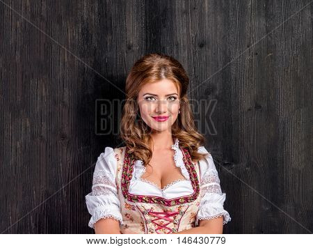 Beautiful young woman in traditional bavarian dress. Oktoberfest. Studio shot on dark wooden background. Copy space.
