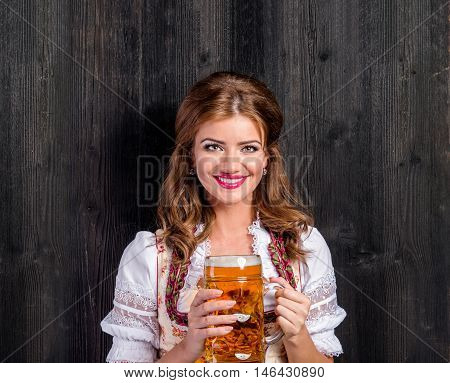 Beautiful young woman in traditional bavarian dress holding a mug of beer. Oktoberfest. Studio shot on dark wooden background. Copy space.