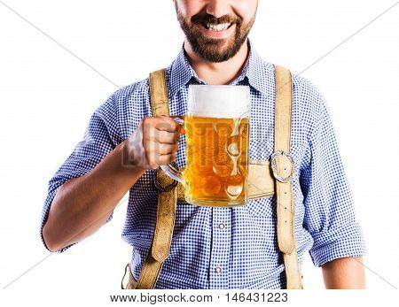 Unrecognizable young man in traditional bavarian clothes holding a mug of beer. Oktoberfest. Studio shot on white background, isolated.