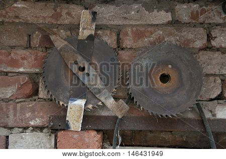 blunt circular saw on a shabby brick wall