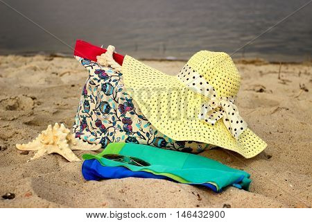 Straw hat, beach bags, sarong, glasses, starfish close-up lying on the beach on sea background.