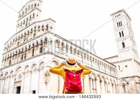Young female traveler in yellow sweater and hat standing in front of San Michele basilica in Lucca old town in Italy. Having great vacations in Lucca. Back view