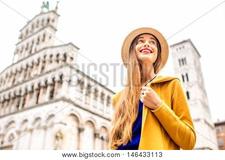 Young female traveler in yellow sweater and hat standing in front of San Michele basilica in Lucca old town in Italy. Having great vacations in Lucca